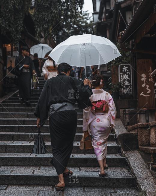 Kyoto, Japan - July 4, 2017: Couple walking together under umbrella