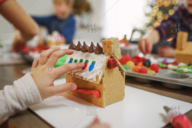Young kids decorating gingerbread houses