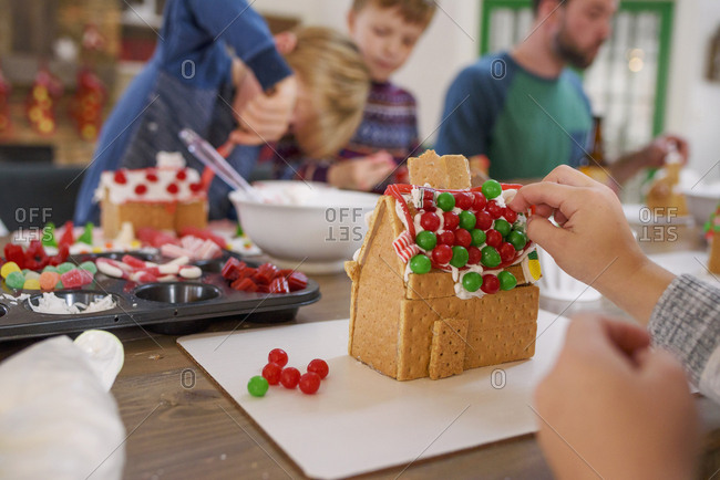A family decorating gingerbread houses