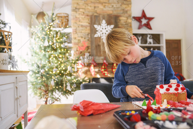 Young boy decorating a gingerbread house
