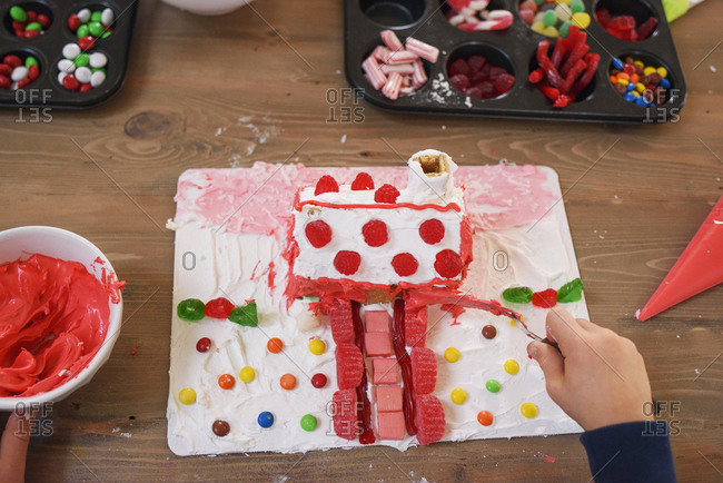 High angle view of kid decorating gingerbread houses