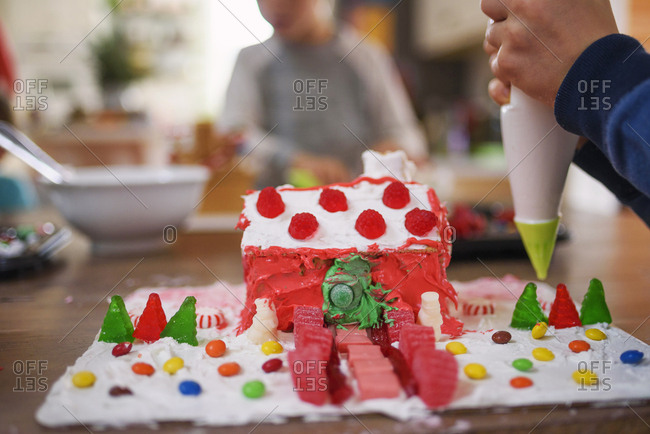 Close up of kids decorating gingerbread houses
