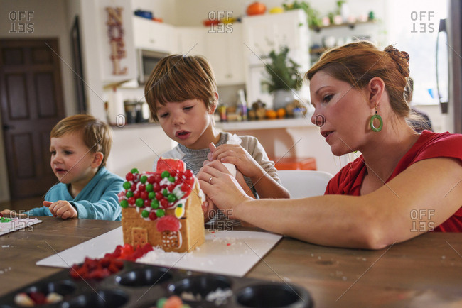 Mother helping boys decorate gingerbread houses