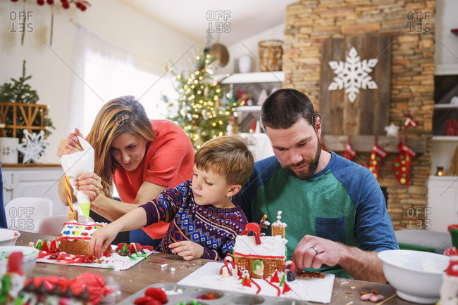 Family decorating gingerbread houses together
