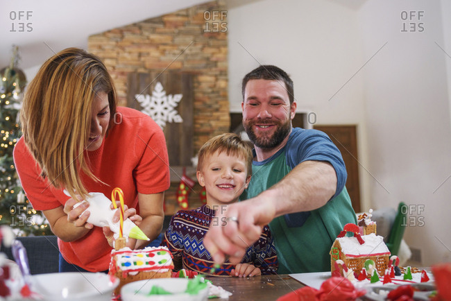 Happy family decorating gingerbread houses together