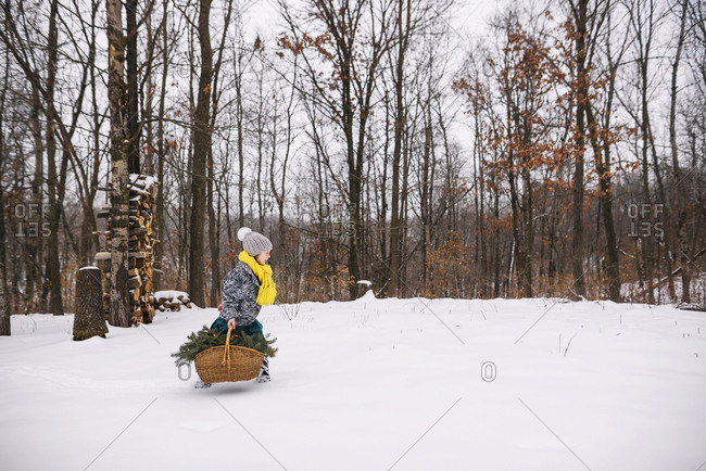 Young girl outside in the snow with basket full of pine boughs