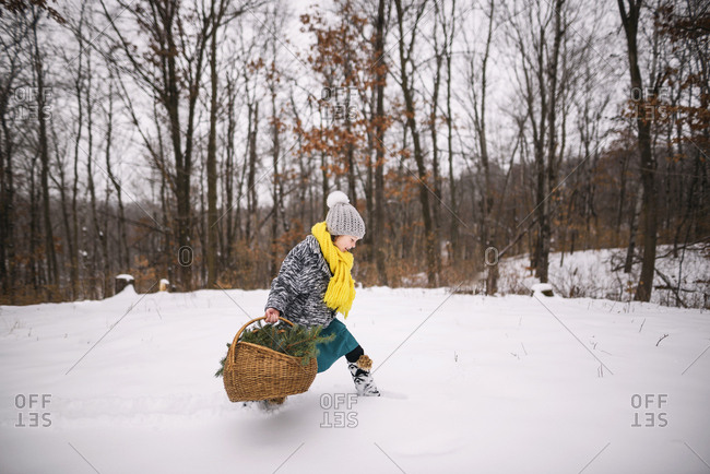 Little girl walking in the snow with basket full of pine boughs