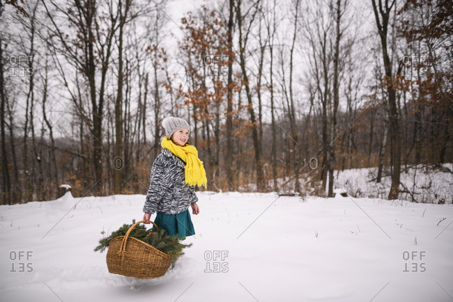 Little girl outside in the snow with basket full of pine boughs