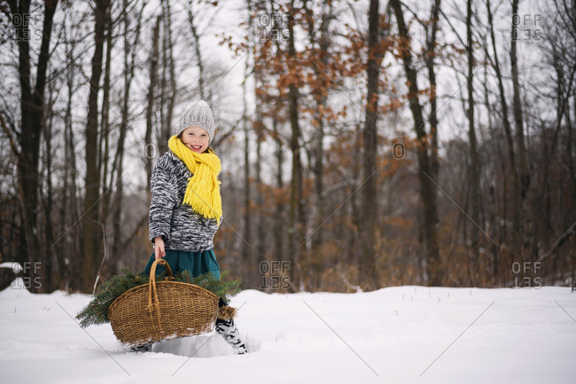 Young girl in the snow carrying basket full of pine boughs