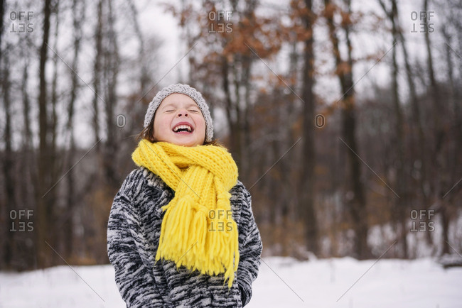Young girl outside in the snow laughing