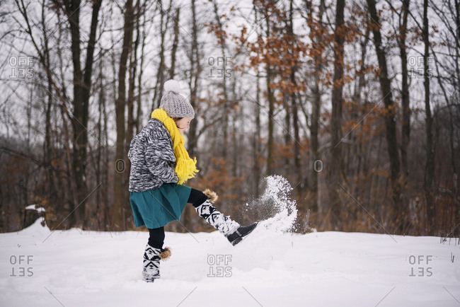 Young girl playing outside in the snow