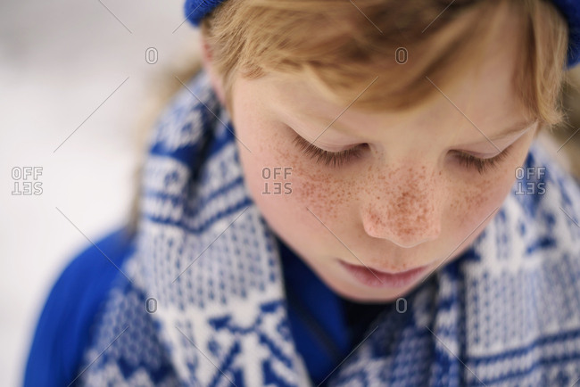 Portrait of young boy looking down outside in the winter