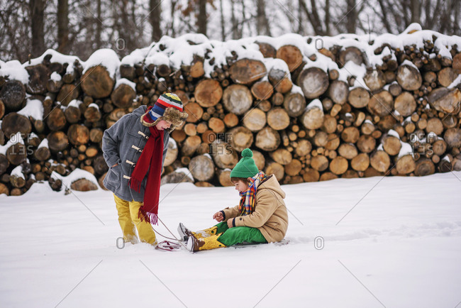 Two young boys playing on sleds outside in the snow