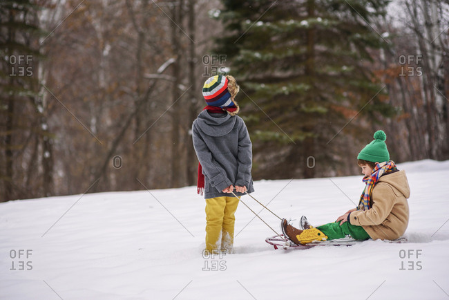 Two brothers playing on sleds outside in the snow