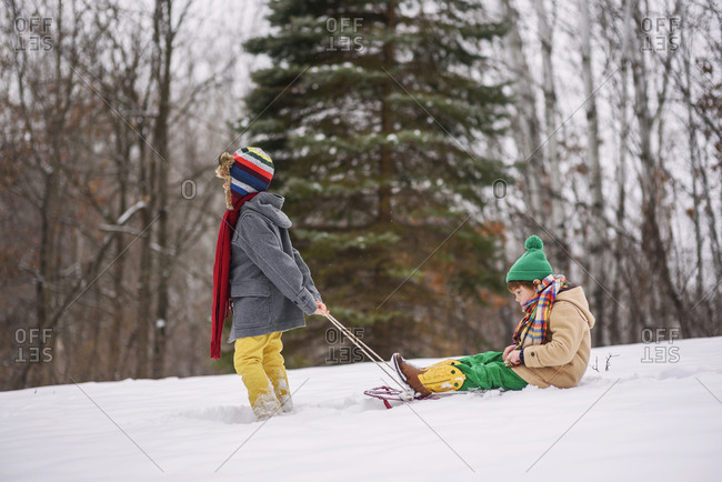 Boy pulling brother on a sled outside in the snow