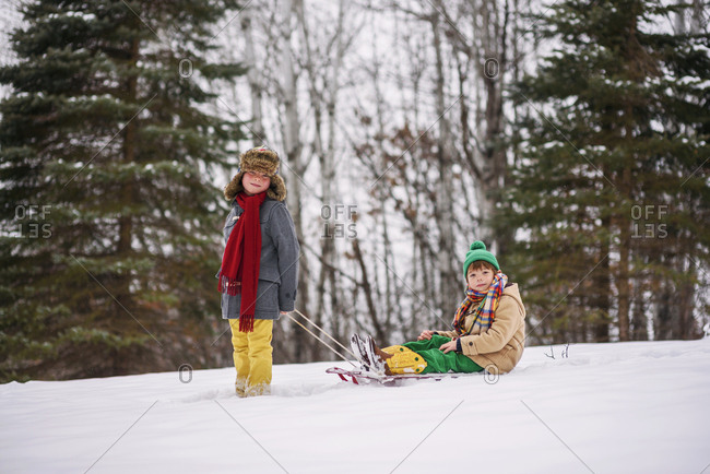 Two young brothers playing on sleds outside in the snow
