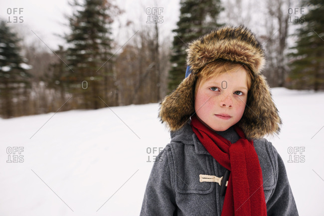 Portrait of young boy standing in the snow