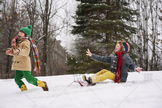 Two boys playing on sleds and throwing snowballs