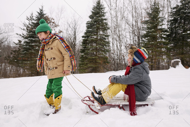 Young boys playing on sleds outside in the snow