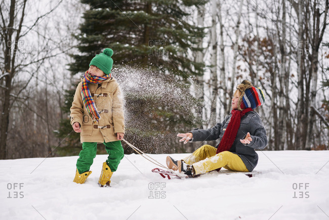 Boys playing on sleds and throwing snow