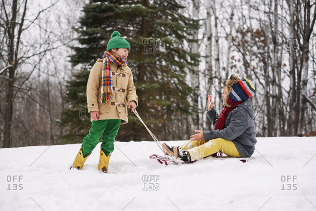 Young boys playing on sleds in the snow
