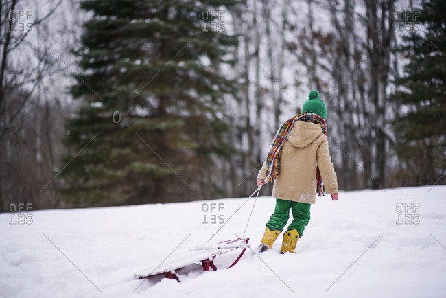 Young boy pulling sled in the snow