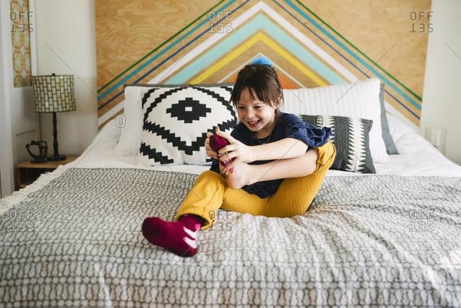 Happy girl putting on socks in bedroom