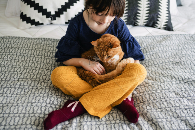 Young girl sitting on bed holding cat