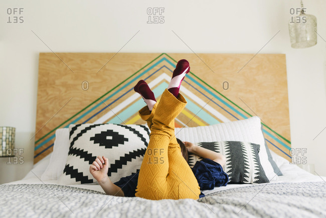 Little girl sitting on bed with her feet in the air
