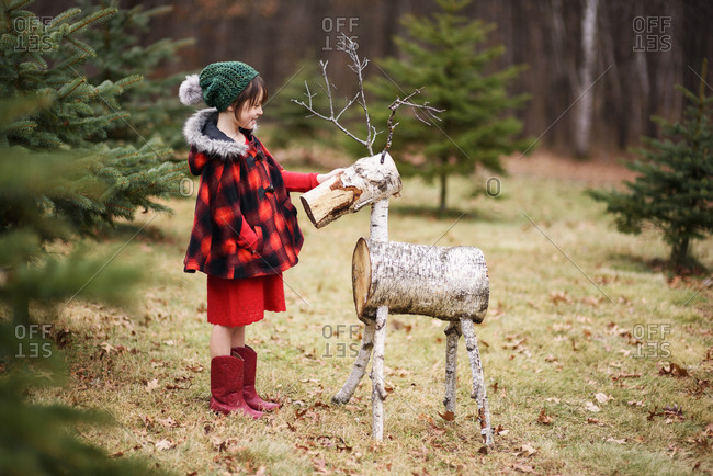 Young girl outside standing by reindeer decoration