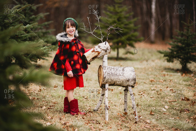 Little girl outside standing by reindeer decoration