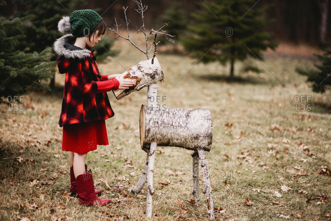 Young girl outside petting a reindeer decoration