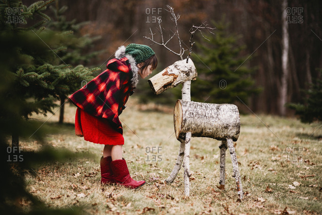 Young girl outside kissing a reindeer decoration