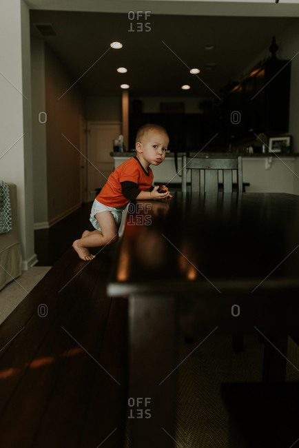Toddler boy eating snack at dining room table