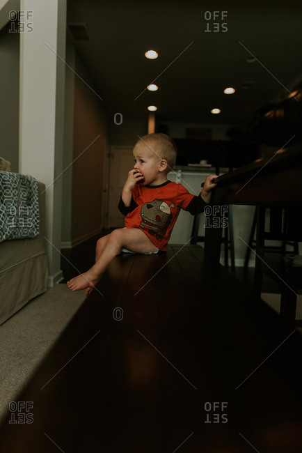Toddler boy eating snack on bench at dining room table