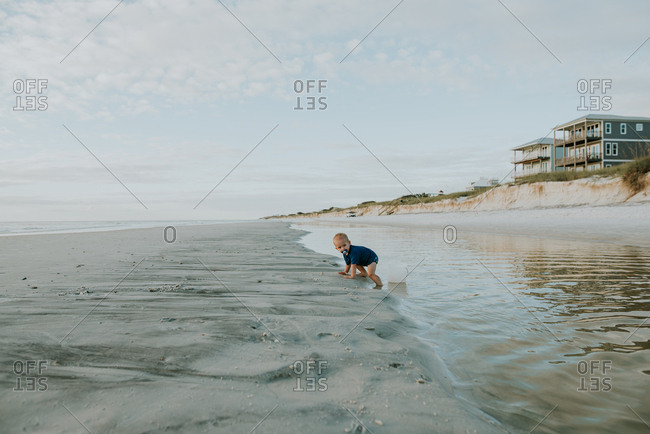 Toddler playing in water on a beach