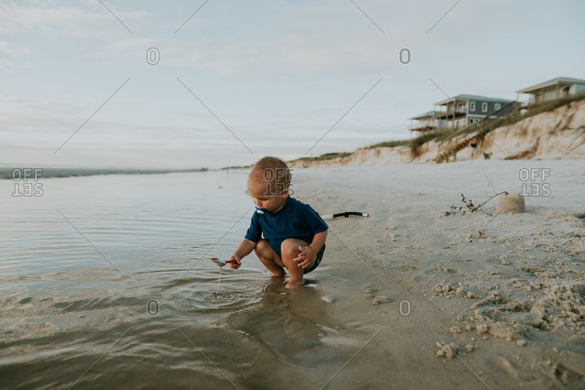 Toddler playing in tide with shovel on a beach