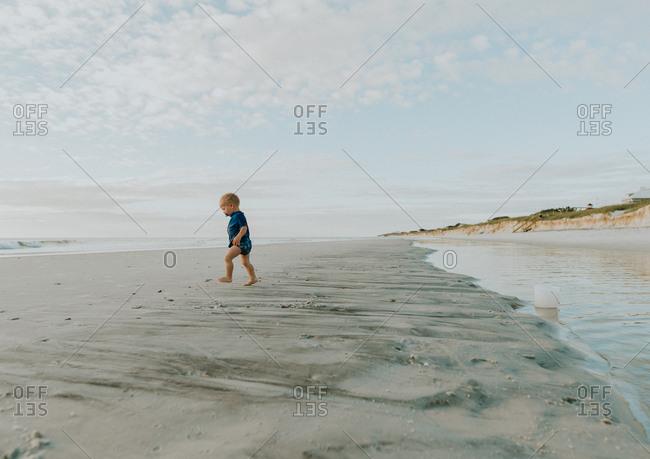 Toddler boy walking on a beach