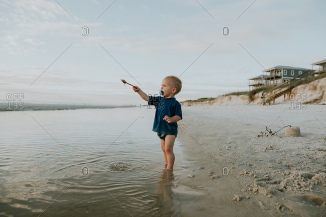 Little boy standing in tide with shovel on a beach