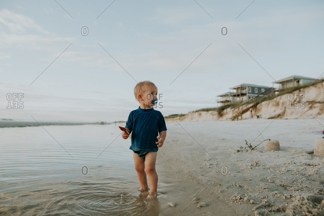 Toddler standing in tide with shovel on a beach