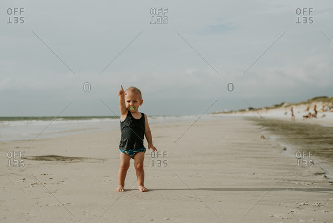 Little boy standing on a beach pointing
