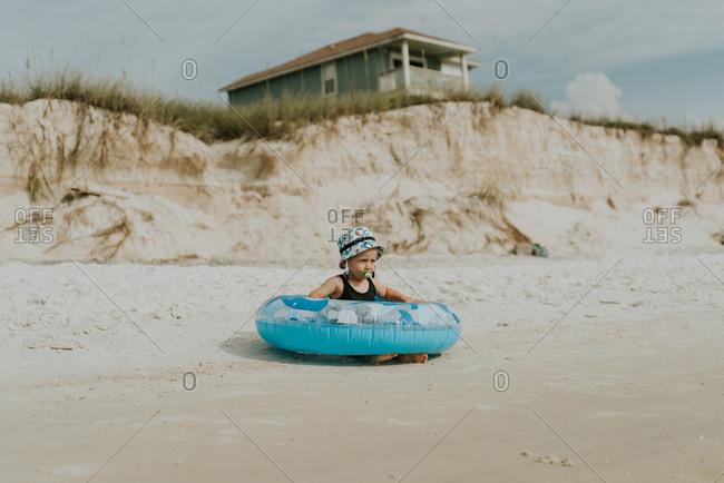 Baby boy sitting in an inner tube on a beach