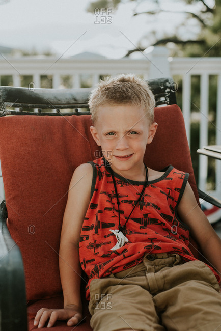 Portrait of a boy sitting on outdoor chair