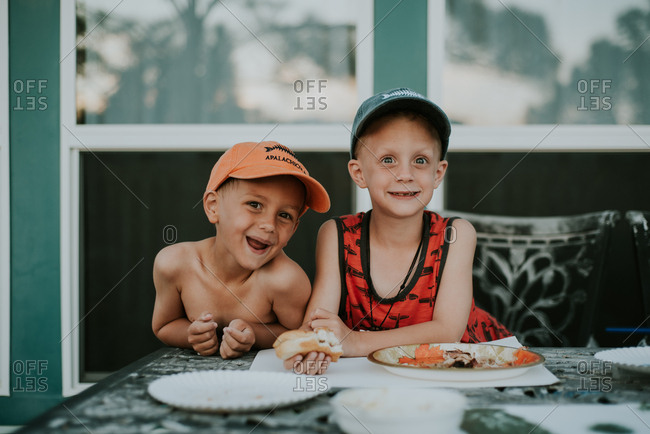 Two boys having lunch on outdoor table