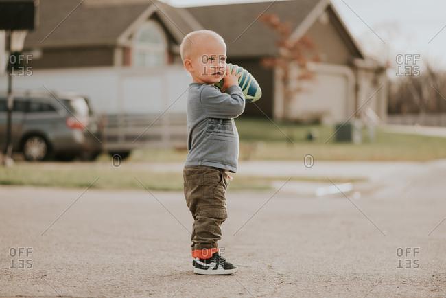 Toddler boy holding football