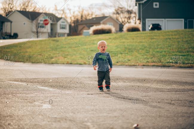Sad toddler boy walking down street