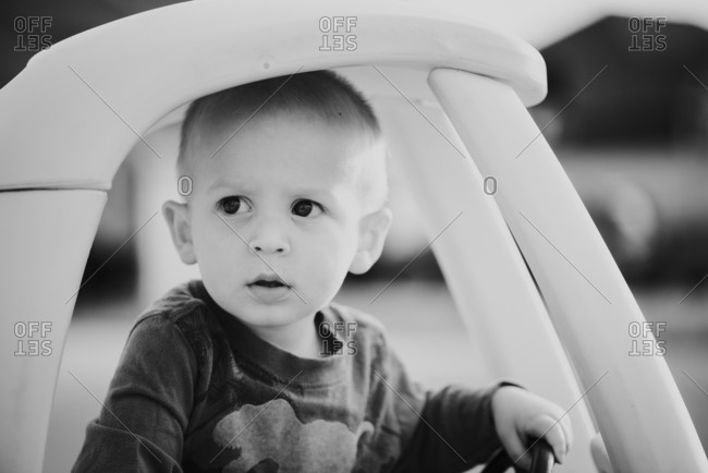 Toddler boy riding in toy car in black and white