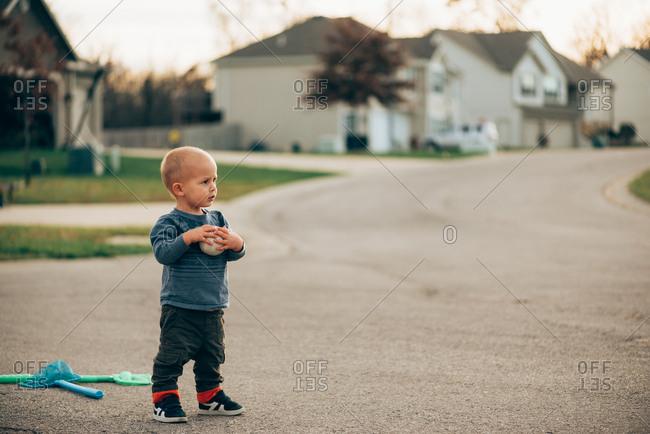 Toddler boy holding baseball