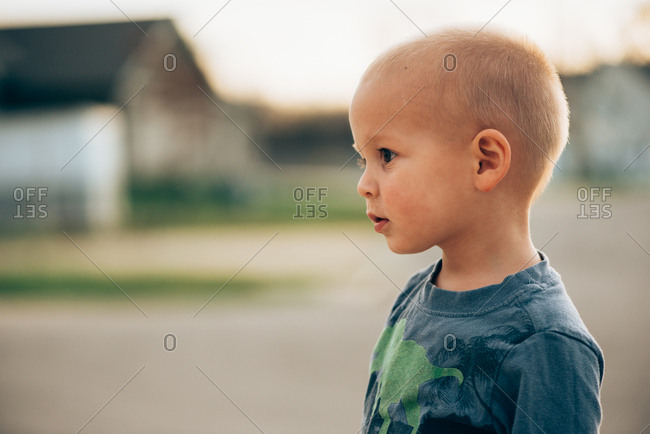 Profile portrait of a blond toddler boy outdoors