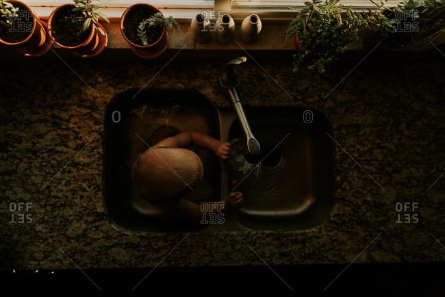 Boy playing in kitchen sink